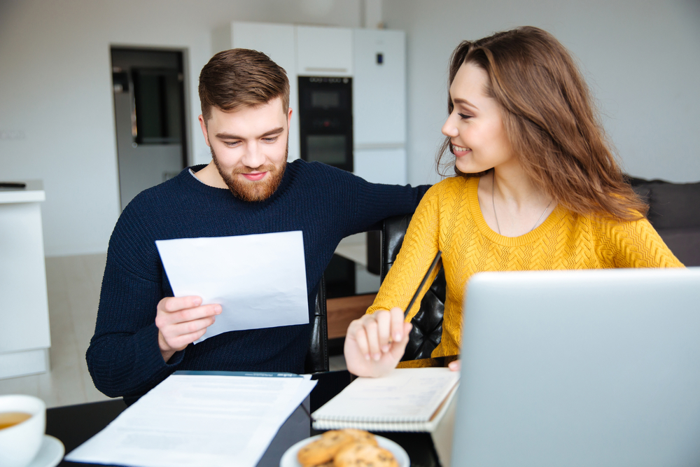 Happy young couple calculating bills at home